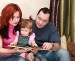 Parents reading book with their baby