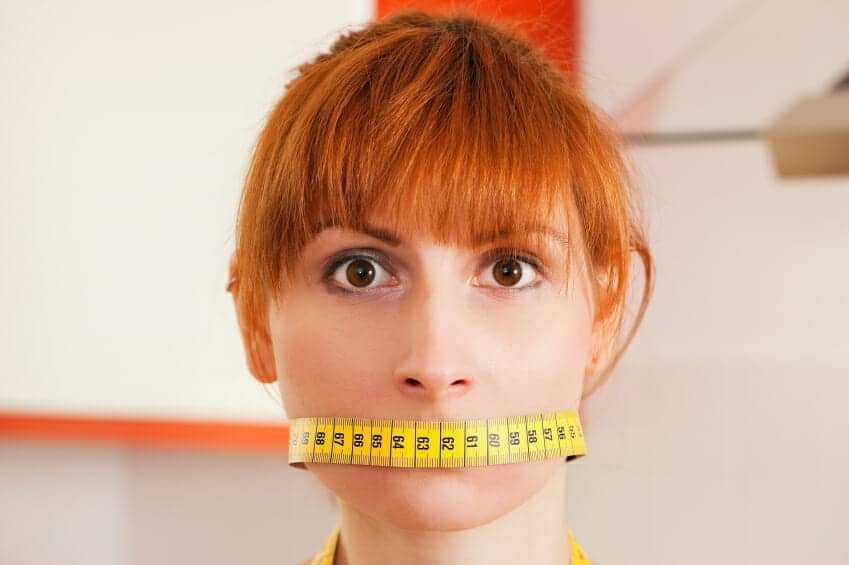 Woman with a measuring tape on her lips