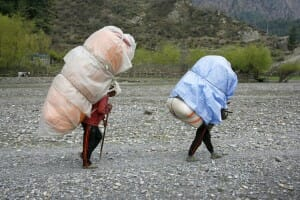 Men carrying heavy loads on back