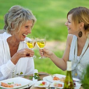 Happy mother and daughter having wine
