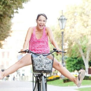 Attractive young tourist woman visting a destination city and riding a bike in a wide avenue, stretching her legs being playful and having a fun and excitement expression, outdoors.