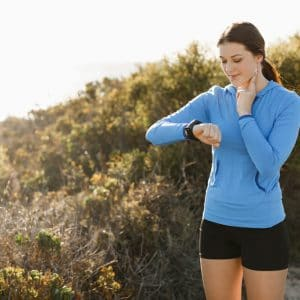 Young runner woman with heart rate monitor running on beach
