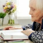 Close-up. Cute, elderly woman with book